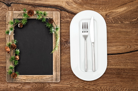 blackboard with christmas tree branches on wooden table. christmas menu concept photo