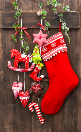 christmas decoration stocking and handmade toys hanging over rustic wooden background photo