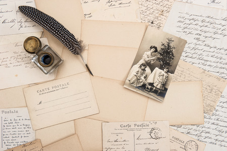 old letters, vintage postcards and antique feather pen. nostalgic sentimental background with retro christmas postcard photo