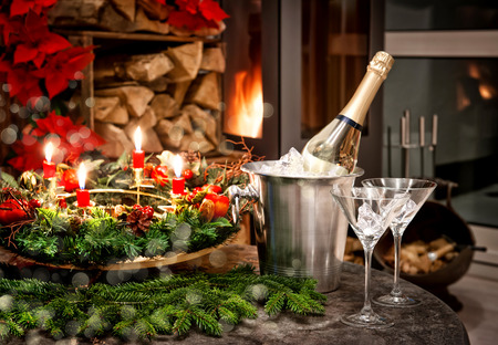 festive home interior decoration for christmas and new year with bottle of champagne and fireplace. candlelight dinner. shiny lights effect photo