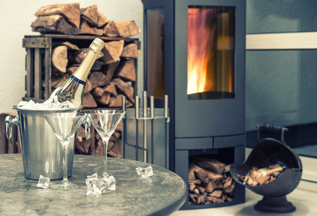 festive home interior wirh champagne, two glasses and fireplace. romantic arrangement. selective focus. retro style toned picture photo