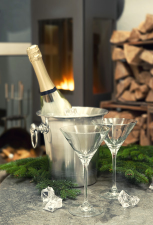 romantic table place setting with champagne, fireplace and fresh christmas tree branches decoration. retro style designed picture. selective focus photo