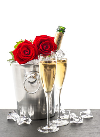 anniversary backgrounds: bottle of champagne, two glasses and red roses. festive arrangement with sparkling wine and flowers