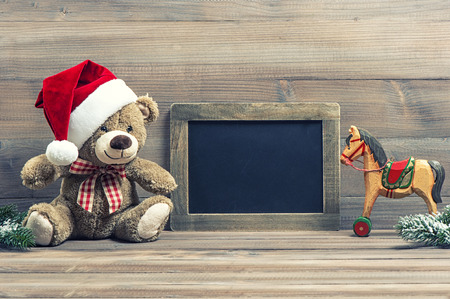 nostalgic christmas decoration with antique toys teddy bear and wooden rocking horse. vintage style picture with blackboard for your text photo