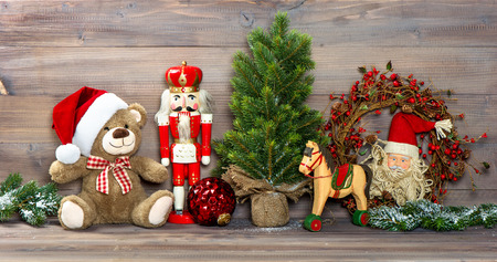 christmas baby: nostalgic christmas decoration with antique toys teddy bear and nutcracker. retro style picture Stock Photo