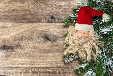 nikolaus: Santa Claus christmas decoration with pine tree branch over rustic wooden background