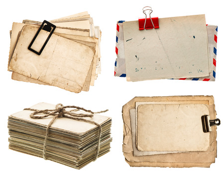 pile of old postcards isolated on white background. vintage paper sheets with clip. air mail envelope. retro design photo