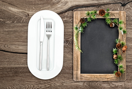 blackboard with christmas tree branches on wooden table. christmas, new years, winter menu concept photo