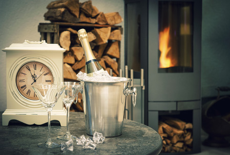 romantic evening with wine: festive New Years home interior with champagne, antique clock and fireplace. selective focus. vintage style dark toned picture