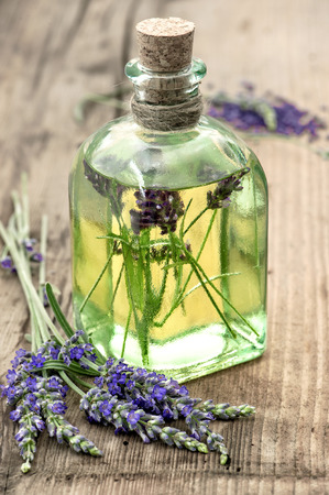 bottle of lavender oil with fresh flowers on wooden background. healthy herbs. selective focus photo
