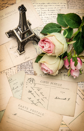 photo story: roses, antique french postcards and souvenir Eiffel Tower from Paris. nostalgic sentimental aged paper background Stock Photo
