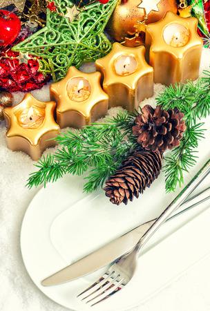 diner aux chandelles: mise d�coration en or, rouge, vert avec des branches d'arbre de no�l festif lieu de table. d�ner aux chandelles. style r�tro image tonique Banque d'images