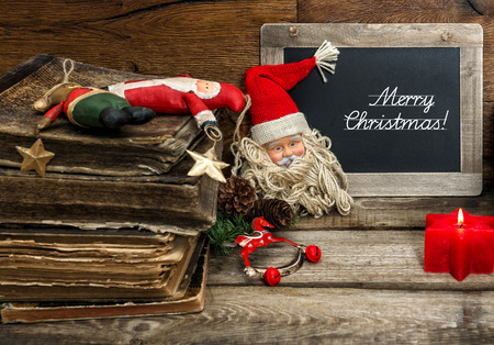 picture book: christmas decoration with antique toys and red candle on wooden background. blackboard with sample text Merry Christmas! selective focus