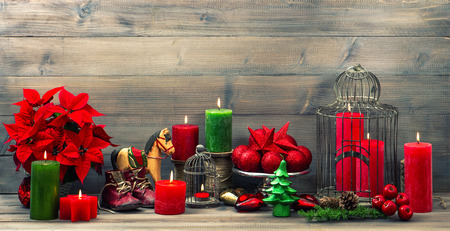 poinsettia: christmas decorations with red candles, flower poinsettia, stars and baubles. vintage style toned picture