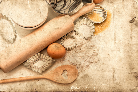 retro: baking ingredients and tolls for dough preparation. flour, eggs, sugar, rolling pin and cookie cutters on white background. retro style picture Stock Photo