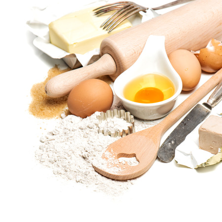 baking ingredients: baking ingredients and tools for dough preparation. flour, eggs, sugar, butter, rolling pin and cookie cutters on white background Stock Photo