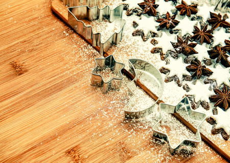 cinnamon stars and cookies cutters on wooden background. vintage style toned picture photo