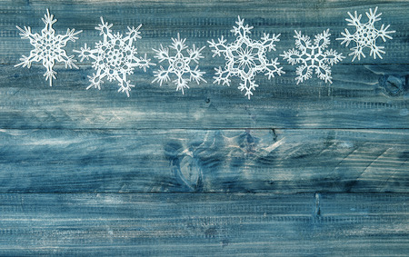 snowflakes border over rustic wooden background. festive winter holidays decoration Stock Photo