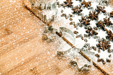cinnamon stars and cookies cutters on wooden background. toned picture with falling snow effect photo