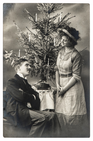 happy young couple celebrated with christmas tree. vintage picture with original film grain and blur