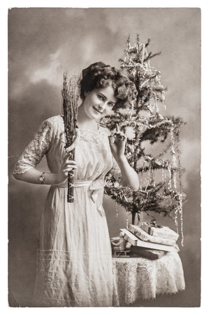 young woman with christmas tree and gifts. antique picture with original scratches and film grain