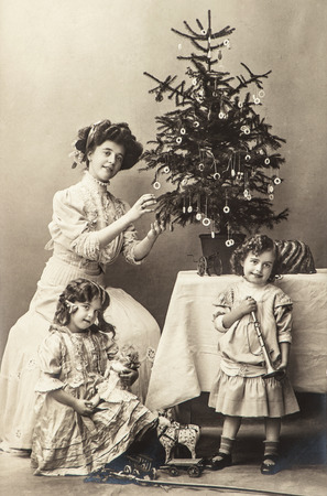 happy mother and children with christmas tree and antique toys. vintage sepia picture with original film grain and scratches Stock Photo