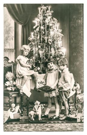 Gelukkige kinderen met een kerstboom, cadeaus en vintage speelgoed. antieke sepia foto met originele film grain