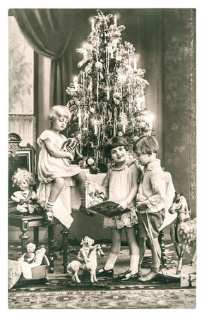 vintage photo: happy kids with christmas tree, gifts and vintage toys. antique sepia picture with original film grain
