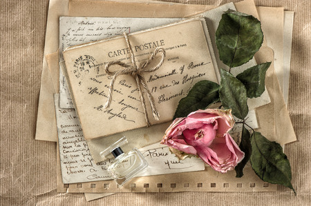french perfume: old love letters, perfume and dried rose flower. nostalgic sentimental scrapbook paper background Stock Photo