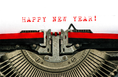 Old typewriter with sample text HAPPY NEW YEAR! Red words on white paper.  photo