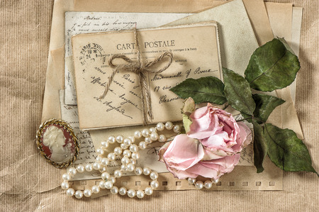 old letters, postcards and vintage things. nostalgic paper background with dry rose flower photo