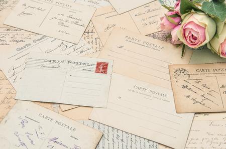 sentimental: vintage postcards and soft rose flowers. nostalgic sentimental background. retro style toned picture