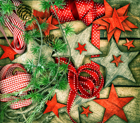 nostalgic: christmas decorations wooden stars and red ribbons for gifts wrapping. nostalgic retro style toned picture Stock Photo