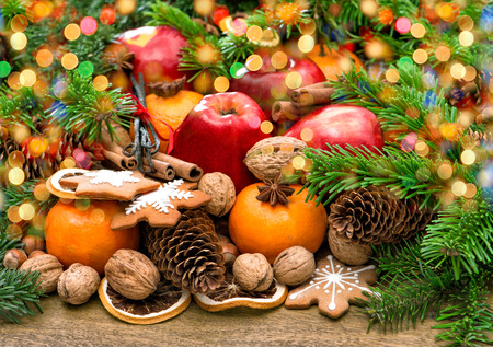 festive food: Fruits, christmas cookies and spices with wonderful lights. Festive food background Stock Photo