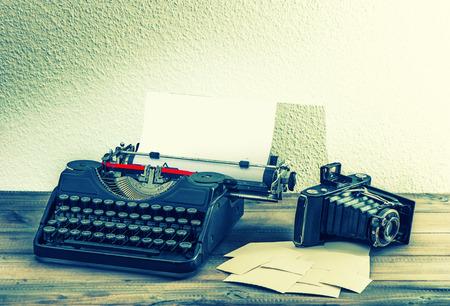 the typewriter: vieja m�quina de escribir y la c�mara de fotos de �poca en el fondo de madera. estilo retro tonificado foto