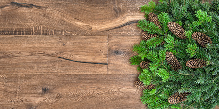 undecorated: christmas tree branches over rustic wooden background. green border from undecorated evergreen twigs Stock Photo