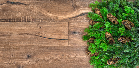 undecorated: christmas tree branches on wooden background. green border from undecorated evergreen twigs with cones Stock Photo