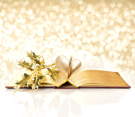golden light: open vintage book with golden pages. bible with golden decoration. shiny lights christmas background Stock Photo