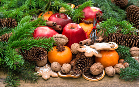 festive food: Apples, tangerine fruits, walnuts, cookies and spices with christmas tree branches. Festive food background
