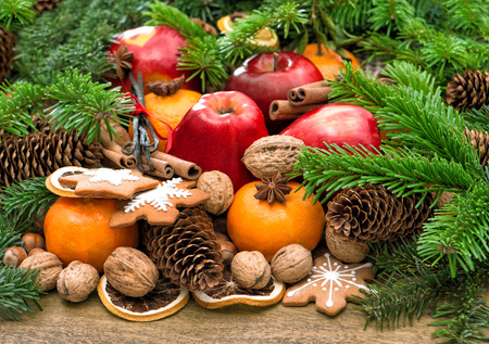 festive food: Apple, mandarin fruits, walnuts, cookies and spices with christmas tree branches. Festive food background