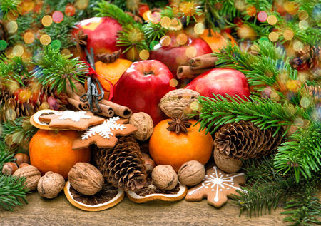 congratulations cards spice: Fruits, nuts, cookies and spices with christmas tree branches. Festive food background with beautiful color lights Stock Photo