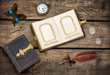 butterfly stationary: antique books, writing accessories and butterfly over rustic wooden background. vintage keys, pocket watch, glasses and feather pen