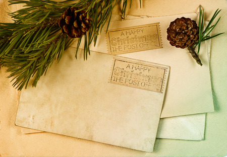 vintage christmas postcard and envelope with pine tree branch decoration. retro style toned picture photo