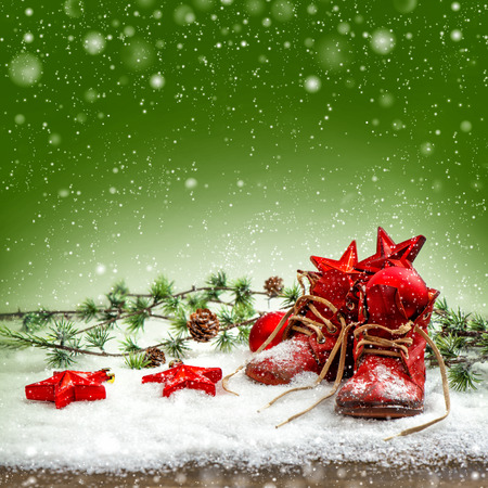 nostalgic christmas: nostalgic christmas decoration with antique baby shoes. festive green background. retro style picture with snow effect Stock Photo