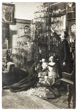親と子のクリスマス ツリーでのヴィンテージの家族の肖像画。元のフィルムの粒子とぼかしアンティーク画像。黒と白の写真