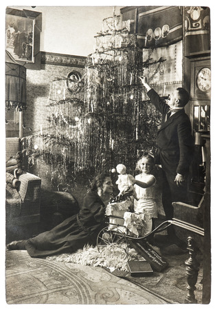 vintage family portrait of parents and child with christmas tree. antique picture with original film grain and blur. black and white photo