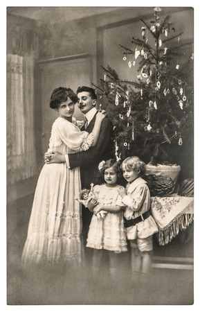 victorian christmas: victorian family parents and children with christmas tree . vintage picture with original film grain and blur