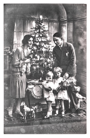 antique family portrait of parents and children with christmas tree. vintage picture with original film grain and blur. black and white photo