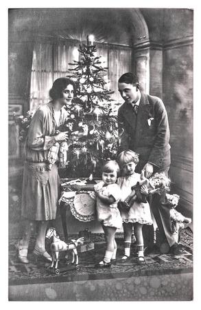 muneca vintage: antiguo retrato de familia de los padres y los niños con el árbol de navidad. foto de la vendimia con grano de la película original y la falta de definición. foto en blanco y negro
