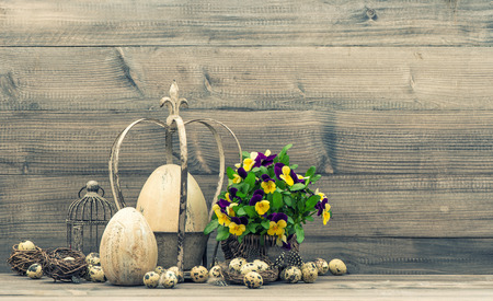 Easter still life with eggs, pansy flowers, nest and birdcage. Vintage style toned picture photo